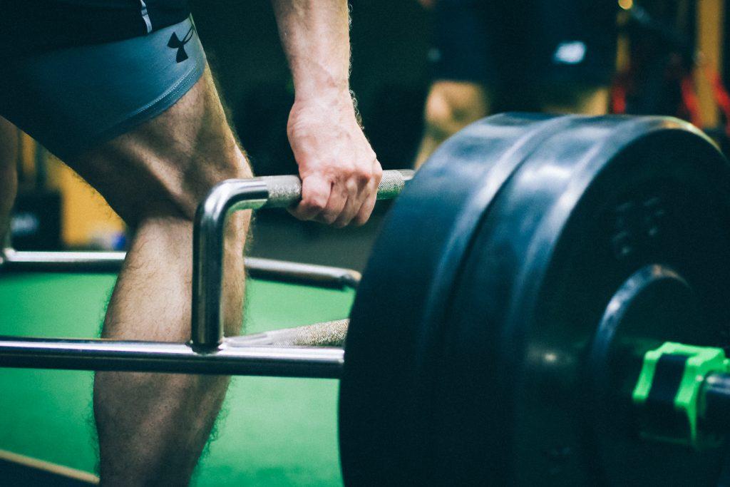 Close up image of a man lifting weight